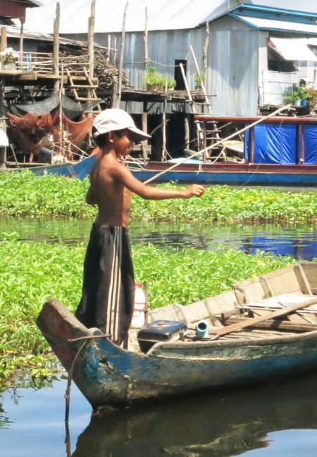 Enfant cambodgien pêchant depuis un bateau.