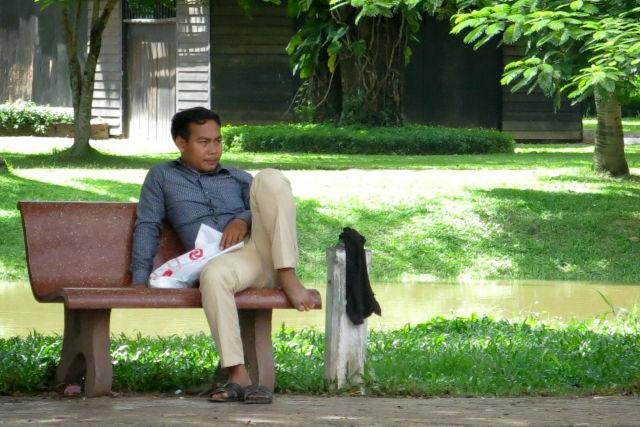 Homme sur un banc dans un parc au Cambodge.